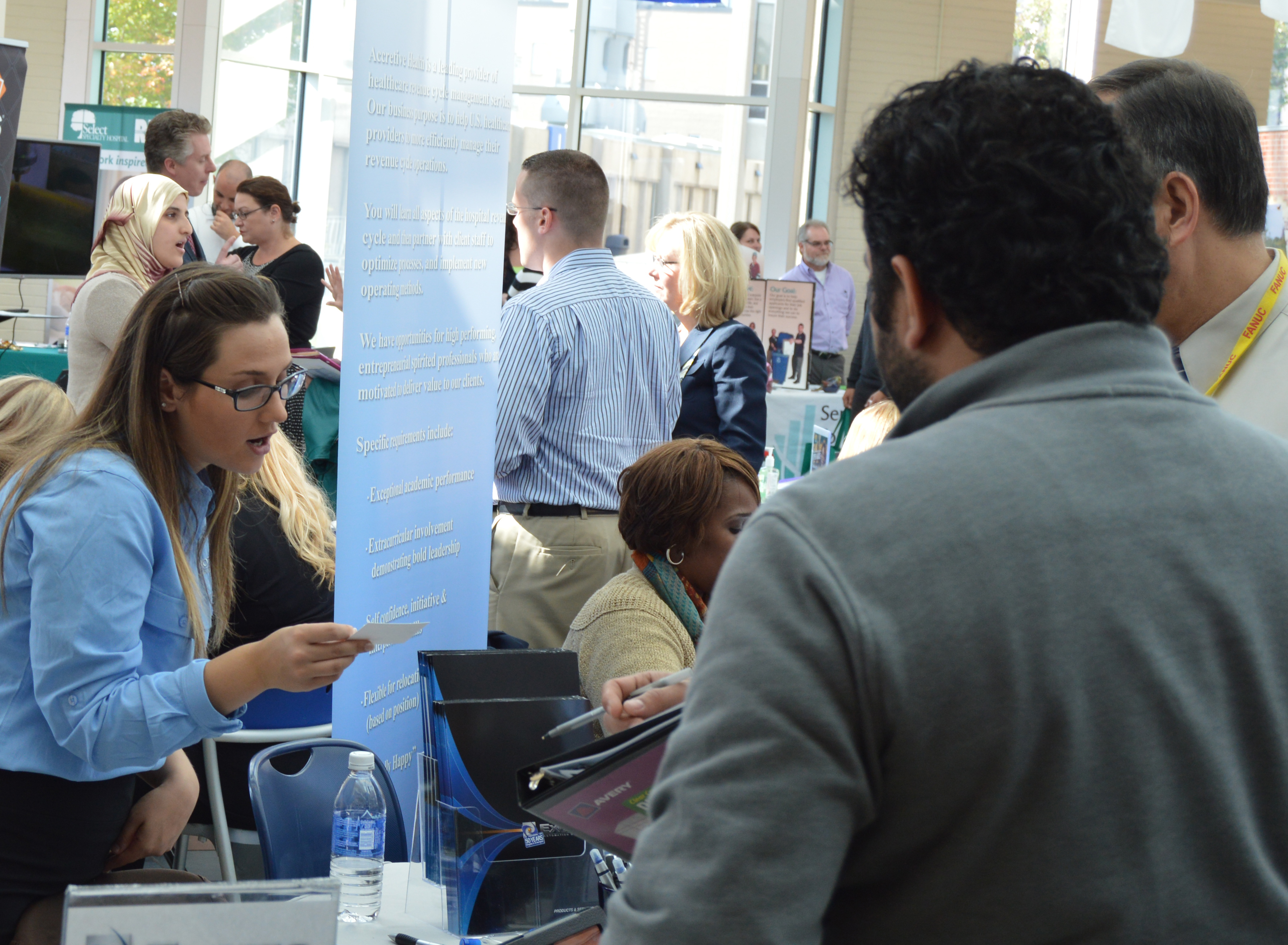 Woman looking at business card at career fair.